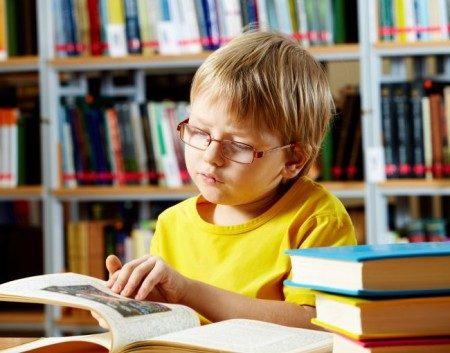 Portrait of child reading book in the library